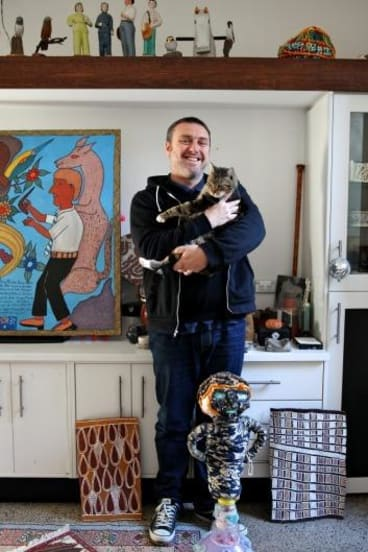 Glenn Barkley at home in Redfern with his collection and moggie.