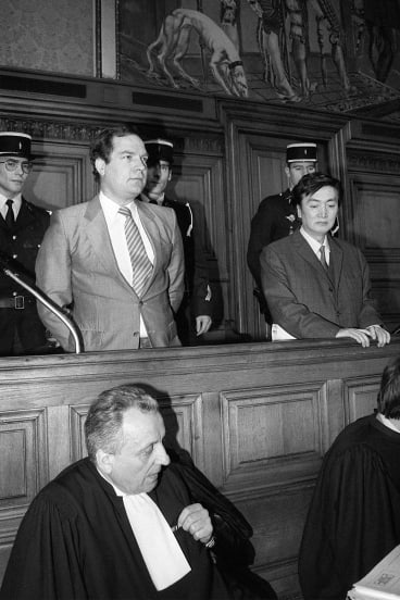 Bernard Boursicot, left,  shares the defendant's box with co-defendant Shi Pei Pu  in May 1986 as their espionage trial opens at Paris Justice Palace.