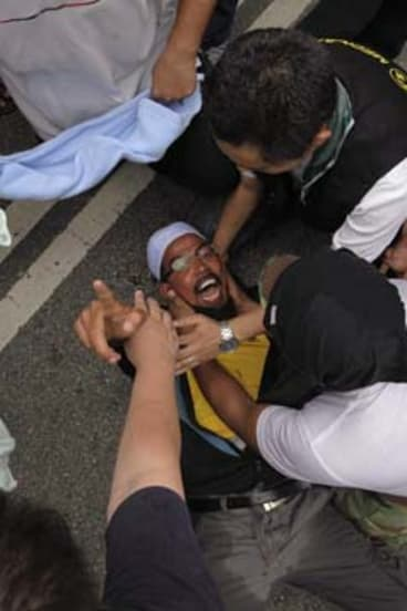 Clash: A tear-gassed protester reacts at an anti-government rally.