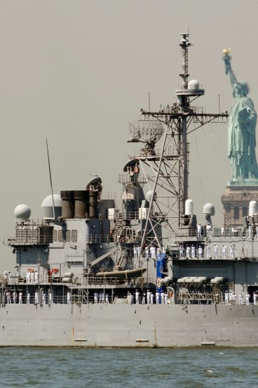 The USS Vella Gulf passes the Statue of Liberty. The new President shows an enthusiasm for military conflict.