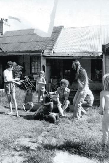 Women and children play in Elsie's backyard.
