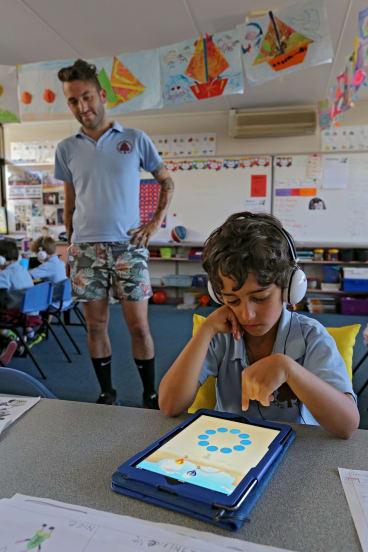 Teacher Matt Serres watches on as grade 1 student Niv Braverman uses the maths  app at Tucker Road Primary.  It works on improving memory.
