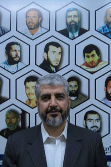 Mishal flanked by a mural of 20 Hamas leaders, fighters and bomb-makers who were killed in Israeli assassinations.