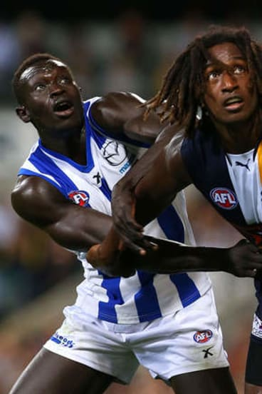 Majak Daw of the Kangaroos and Nic Naitanui of the Eagles contest a boundary throw in.