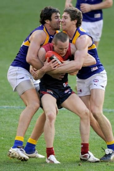 Patrick McGinnity (right) and West Coast teammate Josh Kennedy tackle Melbourne's Tom Scully during their match last weekend.