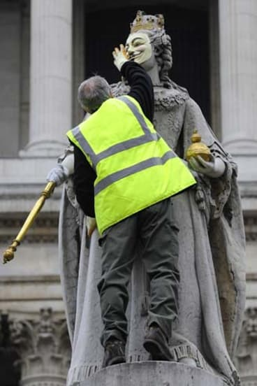 An official removes a mask placed on a statue of Britain's Queen Anne at the 'Occupy' camp outside St Paul's Cathedral.