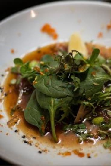 Marinated yellow fin tuna carpaccio with shimeji mushroom and edamame in light citrus dressing, served at Hako.
