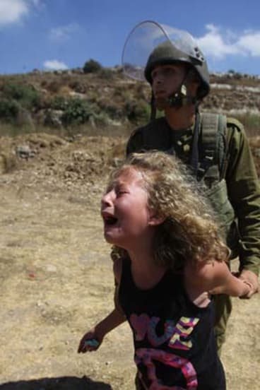An Israeli soldier restrains a Palestinian girl crying over the arrest of her mother   during a  protest over land confiscation  in al-Nabi Saleh.
