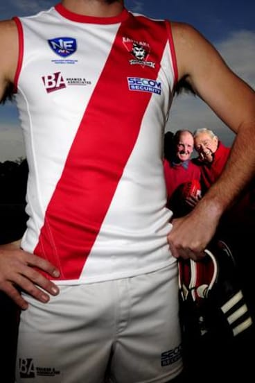 Five-time premiership players Ken 'Butch' King and Neil 'Snakes' Graham pose with the traditional one-off jersey the club will wear in the NEAFL this weekend.