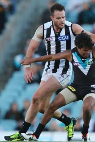Long and short of it: Port little man Jake Neade fights for possession with Magpie Nathan Brown.
