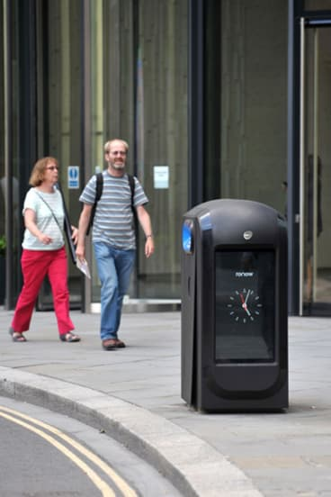 Pedestrians walk past one of the high-tech rubbish bins in London that are capable of collecting smartphone data.