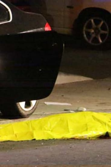 One of the nine crime scenes: A body is covered on the ground after a mass shooting near the campus of the University of California.