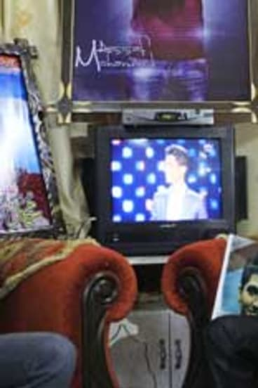Shadi, the brother of Palestinian singer Mohammad Assaf, watches the final of the <i>Arab Idol</i> competition in southern Gaza Strip.