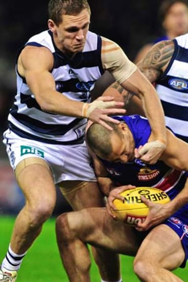 Who's ducking now? Bulldog's Tory Dickson tackled high by Geelong's Joel Selwood.