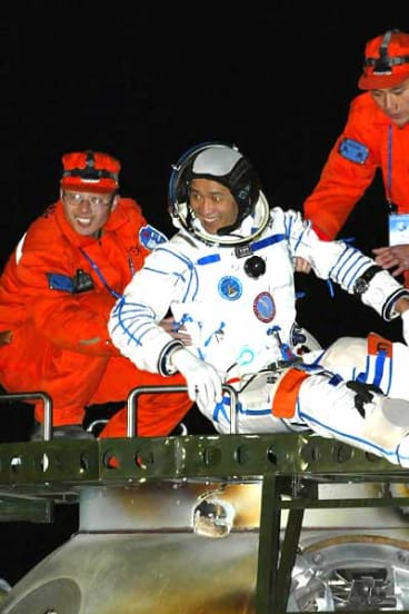 Chinese astronaut Nie Haisheng is helped out of the re-entry capsule of China's second manned spacecraft, Shenzhou VI, in 2005.