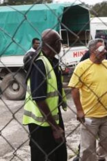 Two asylum seekers, one with an eye injury, leave Manus Island airport following the detention centre violence in which Reza Barati was killed earlier this year.