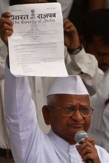 Indian activist Anna Hazare, 73, shows a government notiification to supporters after breaking his hunger strike.