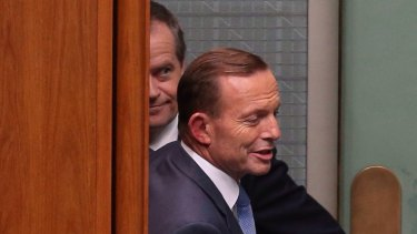Prime Minister Tony Abbott and Communications Minister Malcolm Turnbull pass Opposition leader Bill Shorten behind the Speaker's chair during a division during question time on Thursday.