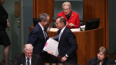 Prime Minister Tony Abbott and Opposition Leader Bill Shorten pass after a divison during question time.
