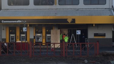 Workers boarding up the front entrance of the Commonwealth Bank on Springvale Rd after a man doused himself in what was believed to be petrol and ignited himself, seriously burning at least five others.