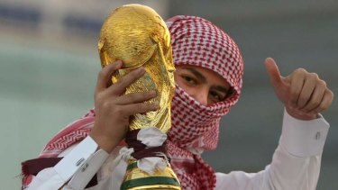 A Qatari youth holds a mock World Cup trophy during celebrations in Doha.