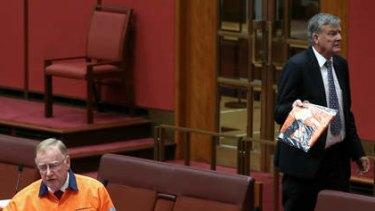Liberal Senator Ian Macdonald speaks on the mining tax repeal as Bill Heffernan storms off. Photo: Alex Ellinghausen