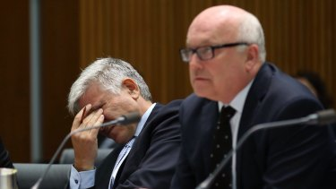 Attorney-General Senator George Brandis and department Secretary Chris Moraitis at a Senate committee hearing in Canberra on Tuesday.