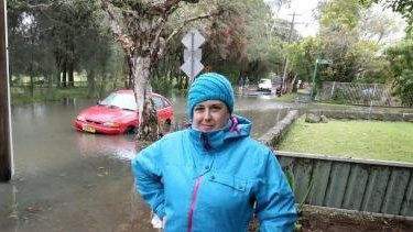 Claire Smith beside the flooded Cooks Rover at Marrickville.