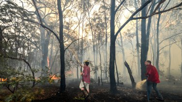 Adam Watkin and partner Prue Mathisen and friends fighting the fire to save their home, near Three Chain rd, Lancefield.