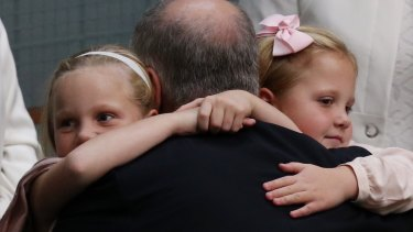 Treasurer Scott Morrison is hugged by his daughters, Lily and Abbey, after he gave the budget address on Tuesday.