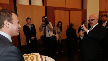 Attorney-General Senator George Brandis takes a photo of Human Rights Commissioner Tim Wilson.