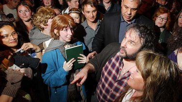 Die hards ... director Peter Jackson, checked shirt, meets fans in Middle Earth costumes at a party in Wellington.