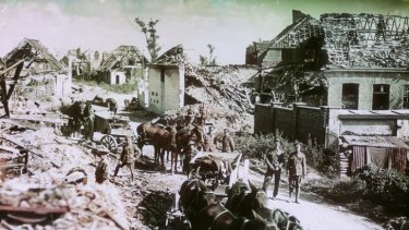 Soldiers, mules and carts at a ruined village.