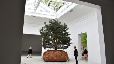 Visitors admire one of the three mobiles trees in French artist Celeste Boursier-Mougenot's work.