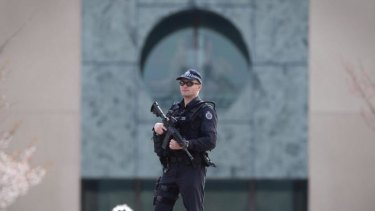 An AFP officer guards the perimeter of Parliament House as the government confirms a man shot dead in Melbourne was a ''known terror suspect''.