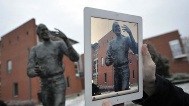 A visitor takes a picture of the statue with an iPad.
