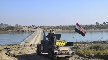 Iraqi forces cross a bridge over the Euphrates supplied by the US Army Corps of Engineers on the approach to Ramadi. Islamic State destroyed the existing bridges across the river as a defensive measure.