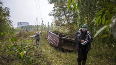 A cooling tower of the Chernobyl Nuclear Power Plant emerges from the forest in the distance as Timothy Mousseau, a biologist, right, measures bat sounds with his assistant.