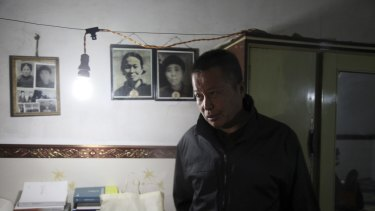 Gao Zhisheng walks past photos of his relatives in a cave home in north-western China's Shaanxi province in this photo taken earlier this year.