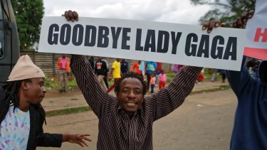 A protester demanding that President Robert Mugabe stands down carries a placard referring to Mugabe's wife Grace Mugabe,