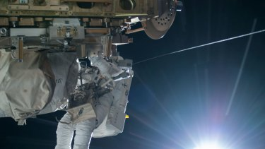 NASA astronaut Terry Virts is seen working to complete a cable routing task while the sun begins to peak over the Earth's horizon on the International Space Station.