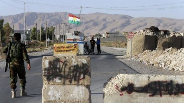 Contested zone: Kurdish Peshmerga fighters man a checkpoint in Makhmour, south of Erbil. Words written on stone slabs by the Islamic State were painted out after it was retaken from them.