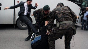 A person identified by Turkish media as Yusuf Yerkel, advisor to Turkish Prime Minister Recep Tayyip Erdogan, kicks a protester already held by special forces police members during Erdogan's visiting Soma, Turkey.
