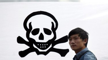 Sometimes civil action reaps dividends. A protester stands in front of a banner in 2012 to protest against plans to expand a petrochemical plant in Zhejiang province. The expansion was suspended.