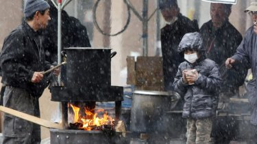 A boy waits for boiled water to cook instant noodle outside a shelter in Sendai, in Miyagi prefecture.