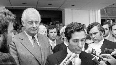 Never again...Gough Whitlam waits as the governor-general's secretary, David Smith, announces the dismissal.