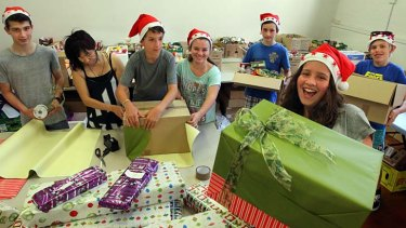 Sweet charity: Giselle Laszok (far right), who has been volunteering with Kids Giving Back, with a Christmas hamper.
