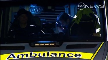Ambulance officers prepare to transport the injured boy to hospital.