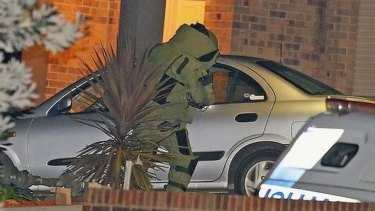 Bomb fears: A police officer in a special suit inspects the dead man's car at the scene on Tuesday night.
