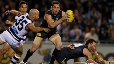 At a stretch: Geelong's Paul Chapman arrives too late to tackle Blues midfielder Heath Scotland.